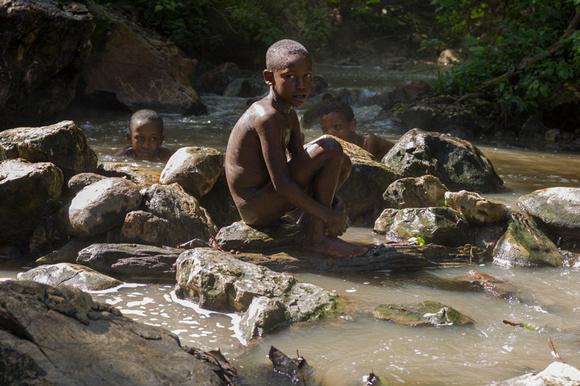 Boy sitting in a hot spring near Bonga in the Kafa region