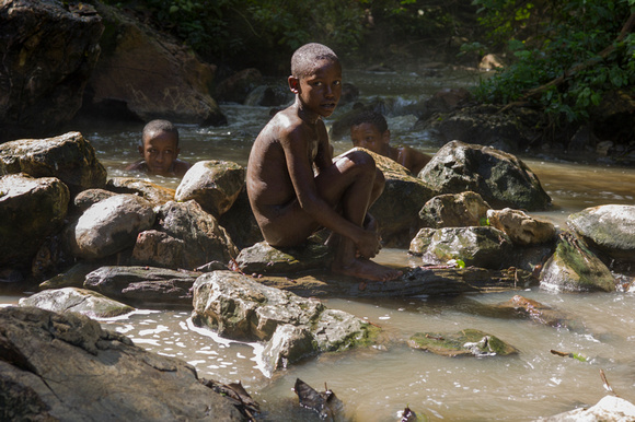 Boy sitting in a hot spring near Bonga in the Kafa region
