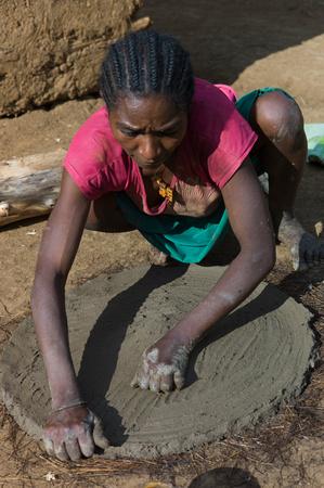 Menja woman making an injira plate